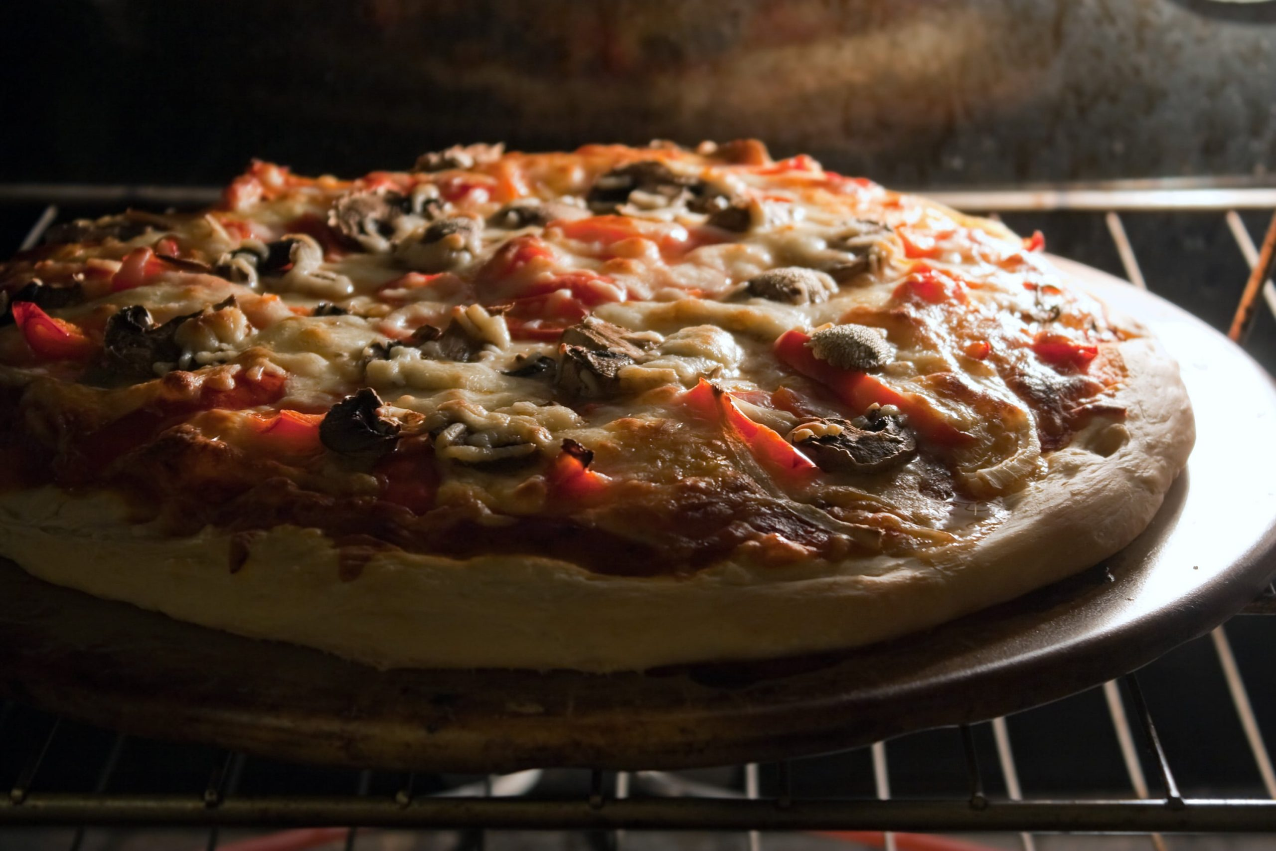 a-fresh-homemade-mushroom-and-pepper-pizza-fresh-out-of-the-oven-and-ready-to-slice-shallow-depth-of-field